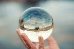 Hand holding a glass ball with reflection of lake. Closeup of hand holding a glass ball with reflection of lake Royalty Free Stock Photography