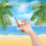 Hand holding a glass on the beach Royalty Free Stock Photos