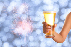 Hand holding a glass of beer with bokeh background Royalty Free Stock Photography