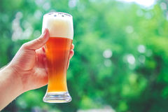 Hand holding glass of beer. On the terrace Royalty Free Stock Images