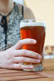 Hand holding glass of beer Royalty Free Stock Photos