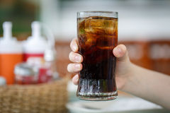 Hand holding glass of cola drink Royalty Free Stock Photo