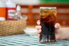 Hand holding glass of cola drink on table Stock Images