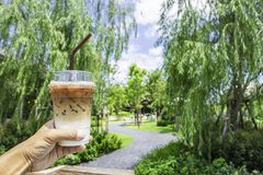 Hand holding a glass of cold espresso coffee Background blurry views tree and road stock photos