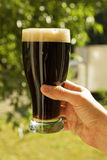 Hand holding glass of dark beer Royalty Free Stock Images