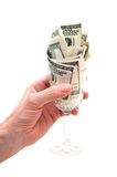 Hand holding glass filled with dollar bills Stock Photo