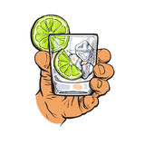 Hand holding glass of gin, vodka, water with ice, lime Royalty Free Stock Photography