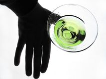 Hand holding glass of Martini. A black silhouetted hand holding onto a glass of green colored martini drink - shot from above on a white illuminated surface stock images