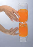 Hand holding glass of orange fluid Stock Photography