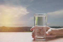 Hand holding a glass of pure water. Hand holding a glass. Of water on table with nature background royalty free stock photos