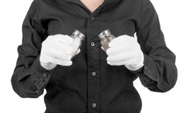 Hand holding glass salt and pepper shakers Stock Image