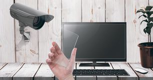 Hand holding glass screen with Security camera watching laptop Royalty Free Stock Photo