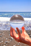 Hand holding glass sphere at beach and sea Royalty Free Stock Photos