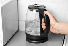 Hand holding a glass teapot with black handle. Close up.  stock photo