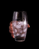 Hand holding glass with water and ice Stock Photos