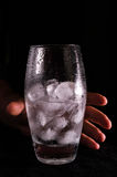 Hand holding glass with water and ice Stock Image