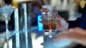 Hand holding a glass of whiskey in bar. Close up. Professional shot in 4K resolution. 086. You can use it e.g. in your commercial video, business, presentation Royalty Free Stock Photography