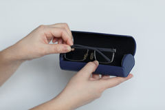 Hand holding glasses and blue case  on white background. Royalty Free Stock Photography