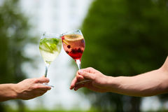 Hand holding glasses cocktail clinking together at outdoor. Royalty Free Stock Photo