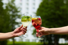 Hand holding glasses cocktail clinking together at outdoor. Stock Photo