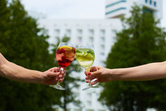 Hand holding glasses cocktail clinking together at outdoor. royalty free stock photos