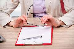 The hand holding glasses at the working desk Royalty Free Stock Photos