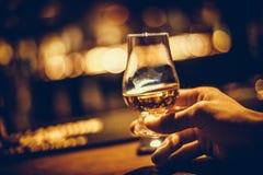 Hand holding a Glencairn single malt whisky glass. Close up shot of a hand holding a Glencairn single malt whisky glass stock images