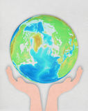 Hand holding globe on hand made paper Stock Photography