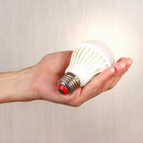 Hand holding a glowing bulb on light wood background Royalty Free Stock Photo