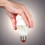 Hand holding a glowing ecofriendly bulb on light wood background Stock Photography