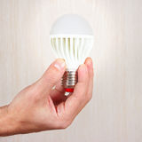 Hand holding a glowing led bulb on light wood background Stock Photo