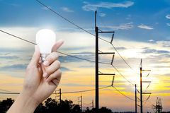 Hand holding a glowing light bulb and electricity pole sunset background Stock Image