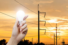 Hand holding a glowing light bulb and electricity pole sunset background Royalty Free Stock Photography