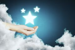 Dream concept. Hand holding glowing star on abstract blue background with cloud. Dream concept Stock Photo