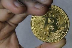 Hand Holding Gold Bitcoin Token.  Royalty Free Stock Photos