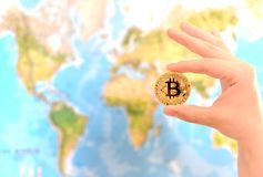 Hand holding gold coin of Bitcoin against map of world. Bitcoin. Concept. New world currency stock photo