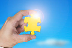 Hand holding gold jigsaw puzzle piece with blue sky sunlight Stock Photography