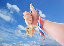 Hand holding gold medal. On sky background Royalty Free Stock Photography