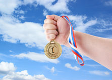 Hand holding gold medal. On sky background Stock Photos