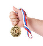 Hand holding gold medal isolated. On white background Royalty Free Stock Image