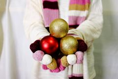 Hand holding gold and red ornament with white sweater, hand glov Royalty Free Stock Photography