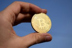 Hand holding golden bitcoin coin on blue sky background royalty free stock image