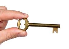 Hand holding golden door key Royalty Free Stock Image
