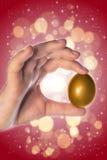 Hand holding a golden egg Stock Photo