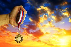 Hand holding a golden medal. Hand holding a golden medal against sunset sky Stock Photo