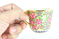 Hand holding a golden thai tea cup Royalty Free Stock Photo