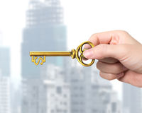 Hand holding golden treasure key in dollar sign shape Royalty Free Stock Images