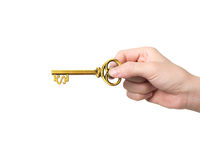 Hand holding golden treasure key in dollar sign shape. On white background Royalty Free Stock Photos