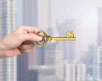 Hand holding golden treasure key in pound symbol shape Royalty Free Stock Photo