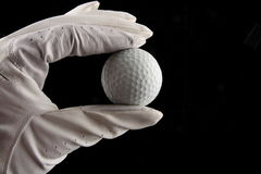 Hand holding golf ball. Hand in glove holding golf ball Royalty Free Stock Images
